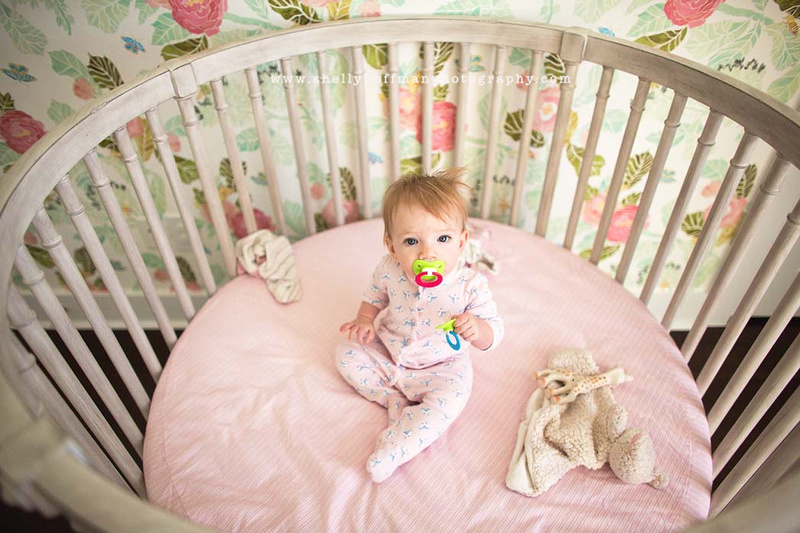 Baby girl in crib after nap with blanket, pacifier and giraffe.