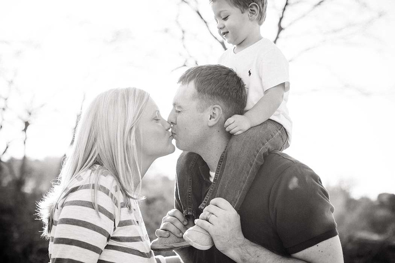 Austin mom and dad kiss with toddler on daddy's shoulders