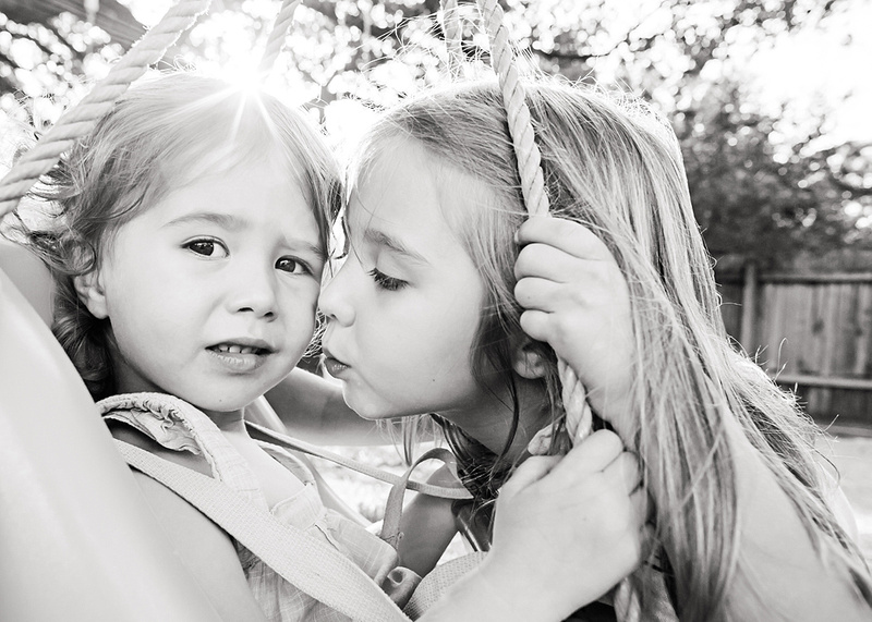 Austin family photographer captures big sister kissing little sister in Austin backyard photos with sunflare.