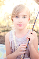 Young blonde and blue-eyed girl with violin bow and sun flare