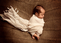 Dreams of planes and trains are still to come. For now, dreams of mommy are enough. Newborn boy in scarf wrap, neutral tones