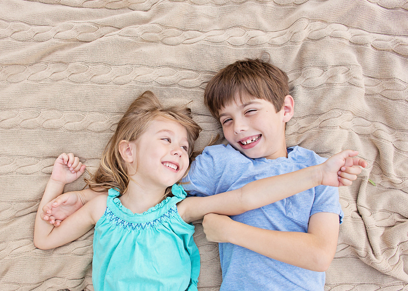 Austin photographer captures giggles with brother and sister stretched out on blanket beachy blanket.